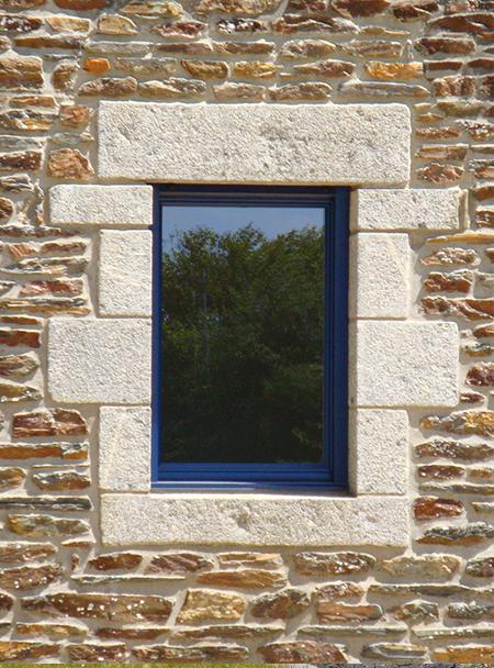 Fenêtre bleue sur mur de pierre